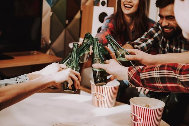 Empresa joven tintineo botellas de cerveza en la fiesta.