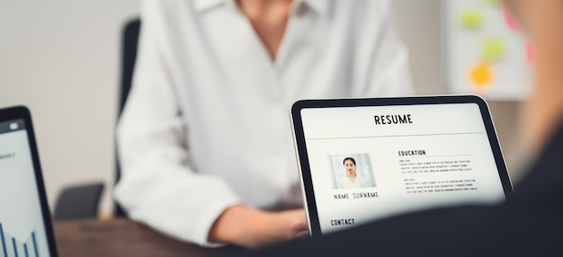 La empresa de recursos humanos (rr.hh.) tiene en la mano una solicitud de currículum en tableta. mujer asiática joven que habla para dar entrevistas de trabajo.