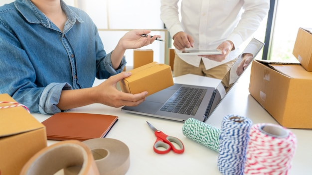 Empresa de reparto pequeña y mediana empresa (pyme) trabajadores caja de embalaje en almacén de distribución oficina en casa para envío al cliente.