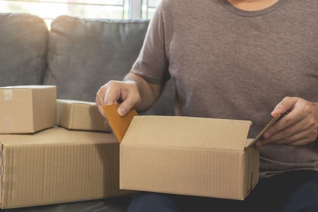 Empresa de reparto pequeña y mediana empresa (pyme) trabajadores caja de embalaje en almacén de distribución oficina en casa