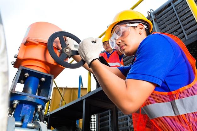 En la empresa de servicios públicos o en la fábrica, dos técnicos o ingenieros que trabajan en una válvula en un equipo técnico de construcción o un sitio industrial