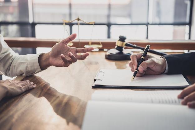 Empresaria y abogados de sexo masculino que trabajan y discuten en un bufete de abogados en el cargo.