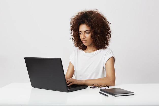 Empresaria africana hermosa que mira la computadora portátil sobre la pared blanca.