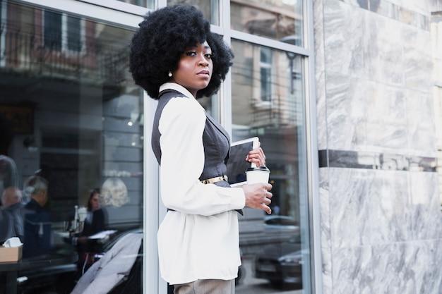 Empresaria africana joven confiada que se coloca fuera de la oficina que sostiene la tableta digital y la taza de café disponible
