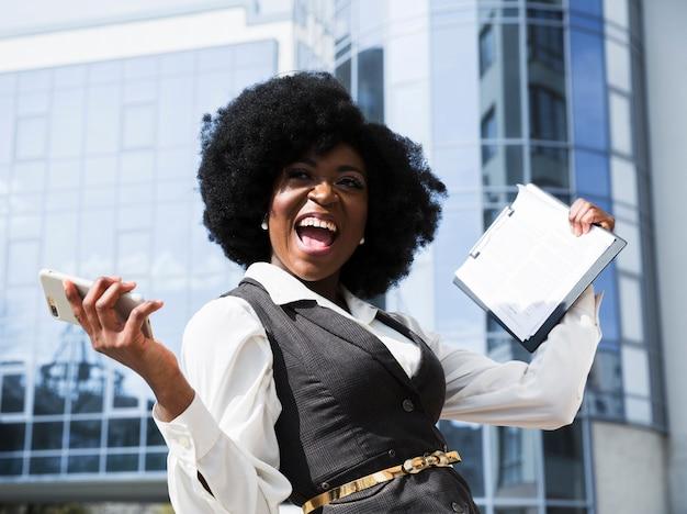 Empresaria africana joven emocionada que sostiene el teléfono móvil y el tablero