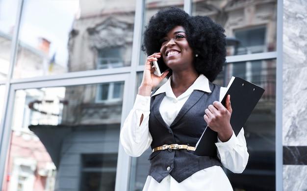 Empresaria africana joven sonriente que habla en el teléfono móvil delante de la puerta de cristal