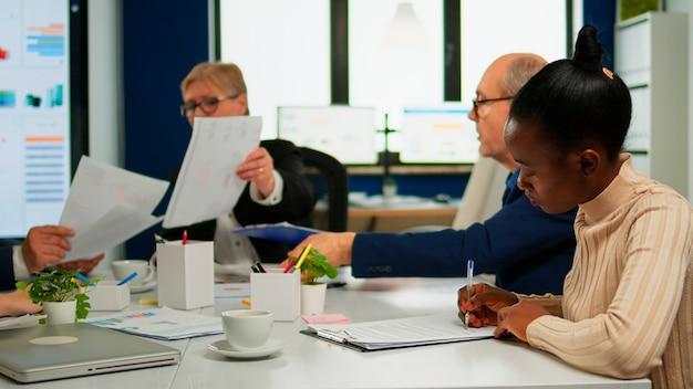 Empresaria africana leyendo documentos, firmando sus socios comerciales mientras comparten el papeleo sentado en la mesa de conferencias en la sala amplia. junta de accionistas del director ejecutivo en la oficina de puesta en marcha