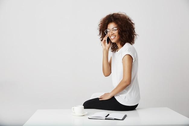 Empresaria africana riendo hablando por teléfono en el lugar de trabajo, recibiendo una llamada de su gerente sobre el arte que hace.