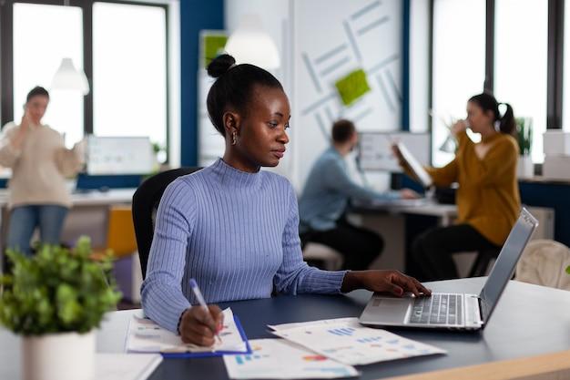 La empresaria africana tomando notas en el portapapeles analizando estadísticas en la oficina de puesta en marcha