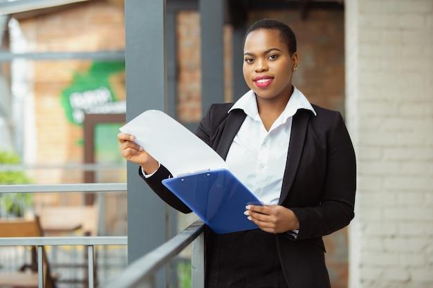 Empresaria afroamericana en traje de oficina sonriendo parece confiado y feliz exitoso