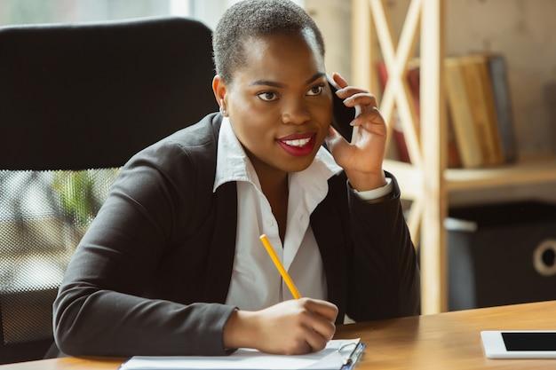 Empresaria afroamericana en traje de oficina sonriendo, se ve confiado y feliz, ocupado
