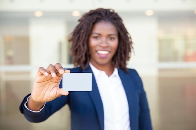 Empresaria alegre que sostiene la tarjeta en blanco