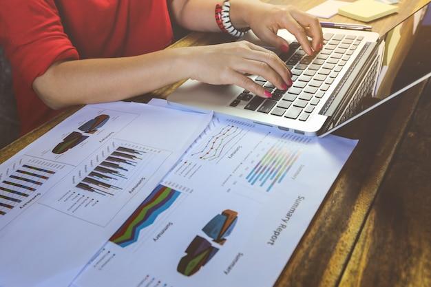 Empresaria analizando gráficos de inversión en papel de documento y usando laptop