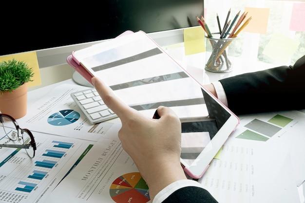 Una empresaria analizando gráficos de inversión en su lugar de trabajo y utilizando su computadora portátil y touch ipad.