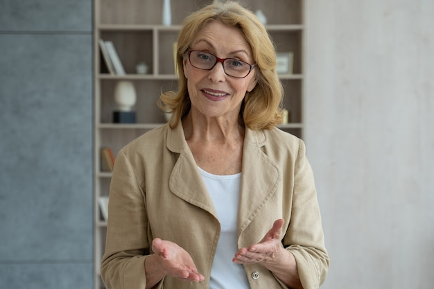 Una empresaria anciana sonriente moderna con gafas haciendo una videollamada mirando a la cámara en línea