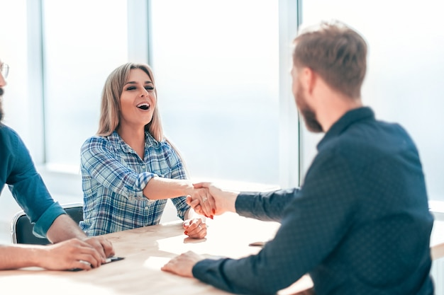 La empresaria un apretón de manos con un nuevo empleado de la empresa.