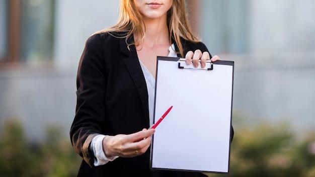 Empresaria apuntando al portapapeles con espacio de copia