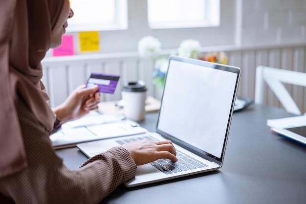 Empresaria árabe hijab marrón comprar en línea con una tarjeta de crédito púrpura en maqueta portátil con pantalla en blanco en casa.
