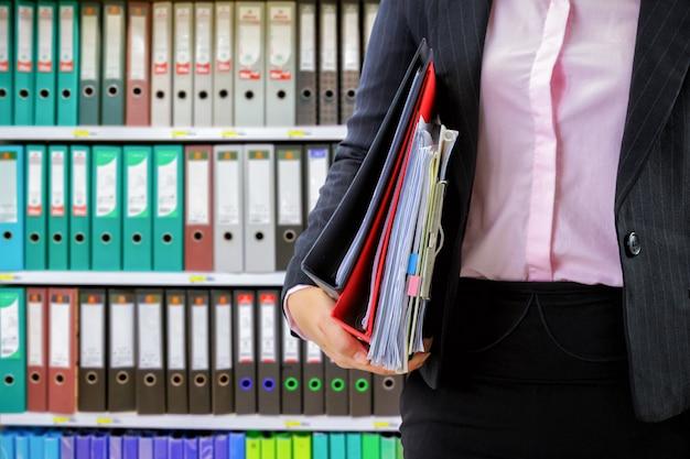 Empresaria con archivos de datos en el fondo de estantes de carpeta