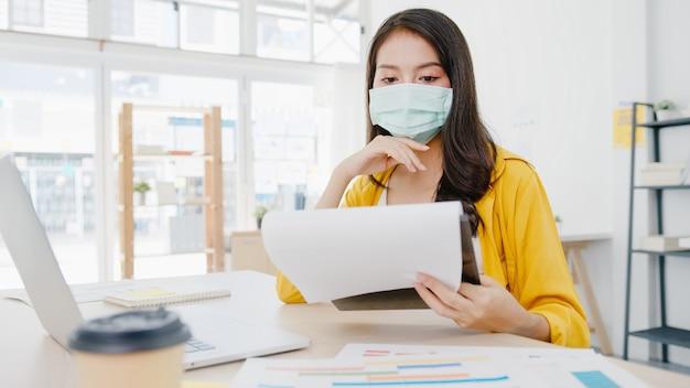 Empresaria de asia que lleva una mascarilla médica para el distanciamiento social en una nueva situación normal para la prevención de virus mientras usa la computadora portátil en el trabajo en la oficina. estilo de vida después del virus corona.
