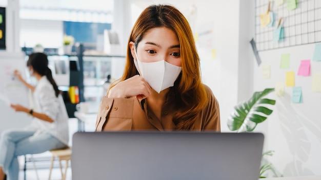 La empresaria de asia usa una mascarilla para el distanciamiento social en una nueva situación normal para la prevención de virus mientras usa la presentación de la computadora portátil a sus colegas sobre el plan en la videollamada mientras trabaja en la oficina.