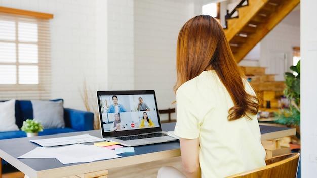 La empresaria de asia usando la computadora portátil habla con sus colegas sobre el plan en la reunión de videollamada mientras trabaja desde casa en la sala de estar autoaislamiento, distanciamiento social, cuarentena para la prevención del coronavirus.