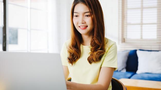 La empresaria de asia usando la computadora portátil habla con sus colegas sobre el plan en la videollamada mientras trabaja de manera inteligente desde casa en la sala de estar. autoaislamiento, distanciamiento social, cuarentena para la prevención del coronavirus.