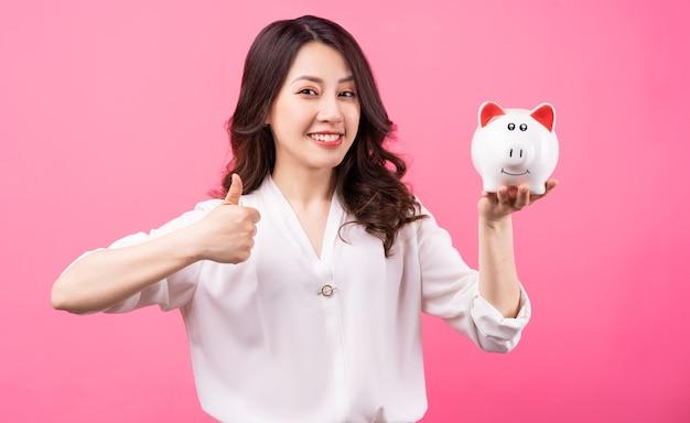 Empresaria asiática con alcancía en la mano, concepto de ahorro de dinero