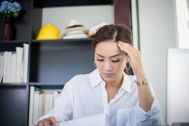Empresaria asiática y alumna seria sobre el libro de lectura y trabajo duro hasta el dolor de cabeza