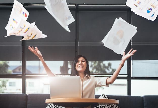 Empresaria asiática de la belleza que lanza papeleo en el aire. exitoso y logro