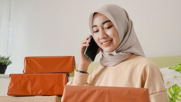 Empresaria asiática feliz de servir a los clientes en línea