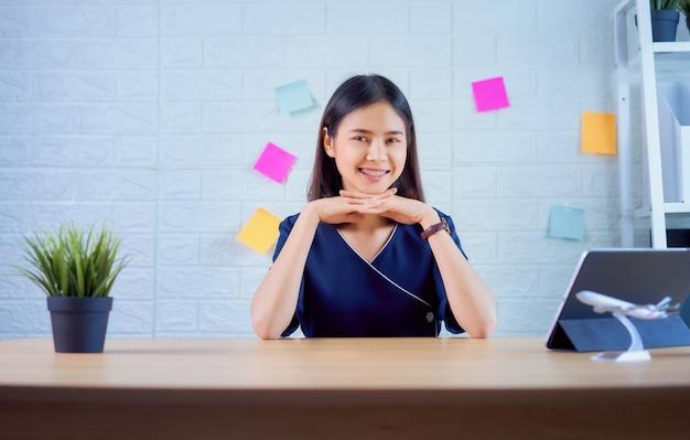 Empresaria asiática feliz trabajando en tableta en la mesa en la oficina en casa.