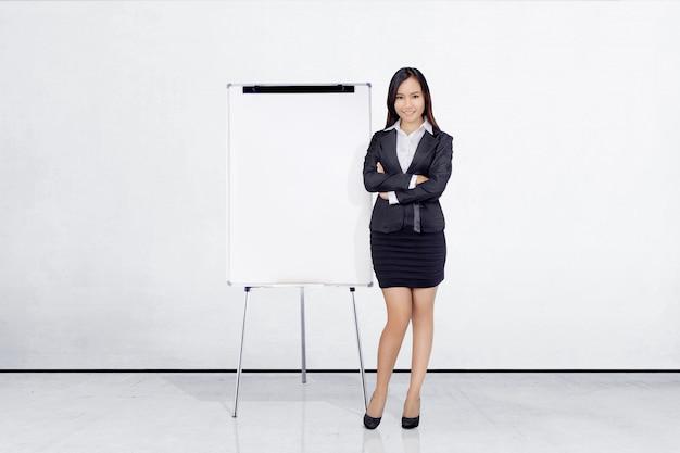 Empresaria asiática hermosa que se coloca con whiteboard