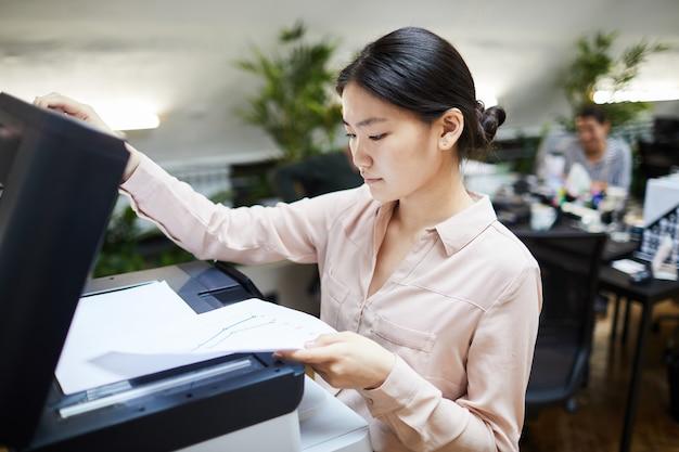 Empresaria asiática imprimir documentos en la oficina