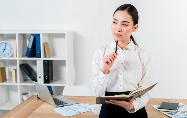Empresaria asiática joven contemplada que se coloca delante del escritorio que sostiene el diario y la pluma disponibles