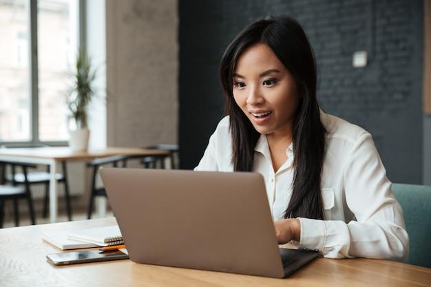Empresaria asiática joven emocionada que usa la computadora portátil