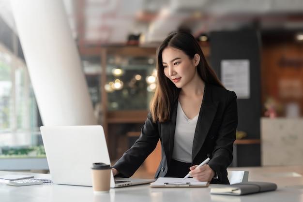 La empresaria asiática joven está sentada en la oficina usando una computadora portátil y tomando notas.