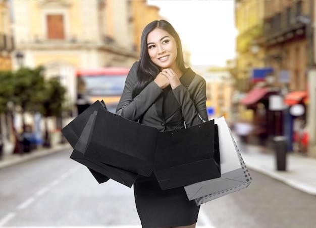 Empresaria asiática llevando bolsas de compras en la ciudad