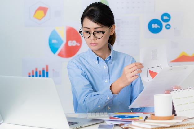 Empresaria asiática prestar atención mientras se trabaja - conceptos de negocios y finanzas.