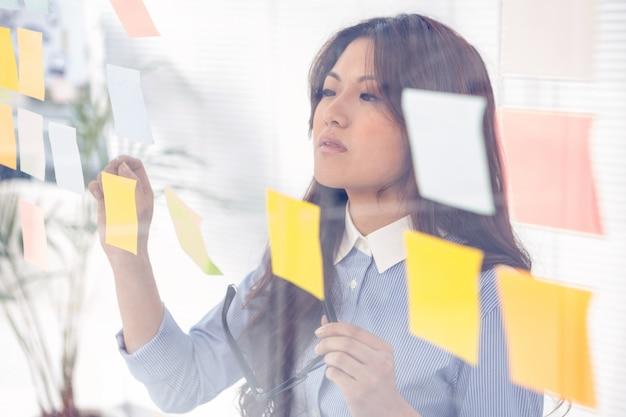 Empresaria asiática que usa notas pegajosas en la pared en oficina