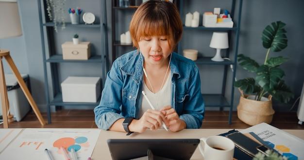 La empresaria asiática que usa la tableta hable con sus colegas sobre el plan en una videollamada mientras trabaja desde su casa en la sala