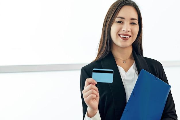 Empresaria asiática con una tarjeta de crédito en blanco.