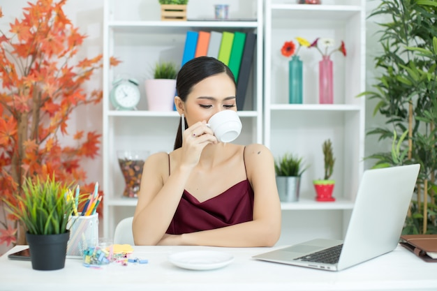La empresaria asiática toma un descanso para tomar café después de trabajar en la computadora de computadora portátil en el escritorio
