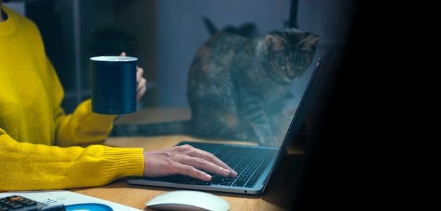 Empresaria asiática tomando café y usando una computadora portátil en su escritorio por la noche. concepto de horas extras de trabajo.