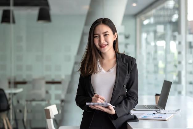 Empresaria asiática tomando notas en la oficina.