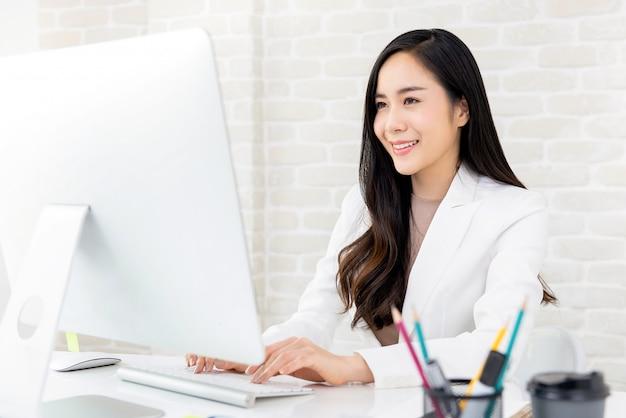 Empresaria asiática trabajando en la computadora en la oficina