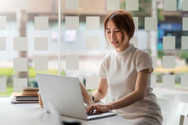 Empresaria asiática trabajando escribiendo trabajo en el teclado de la computadora portátil en la oficina.