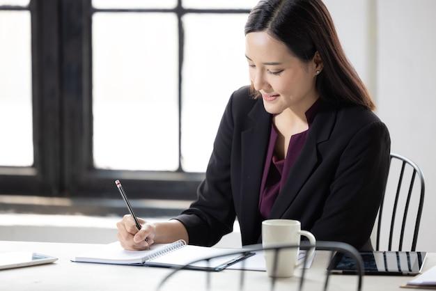 Empresaria asiática trabajando en el papeleo de la mesa