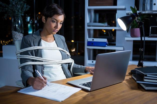 Empresaria atada con una cuerda mientras trabajaba en la computadora portátil en su escritorio