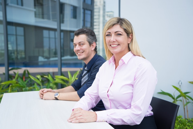 Empresaria atractiva confiada positiva y su ayudante que se sientan en la tabla